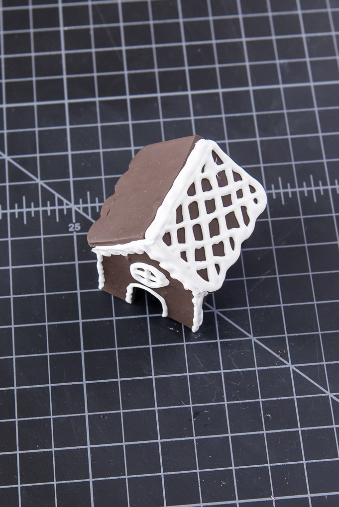 brown and white decorated mini gingerbread house made out of clay