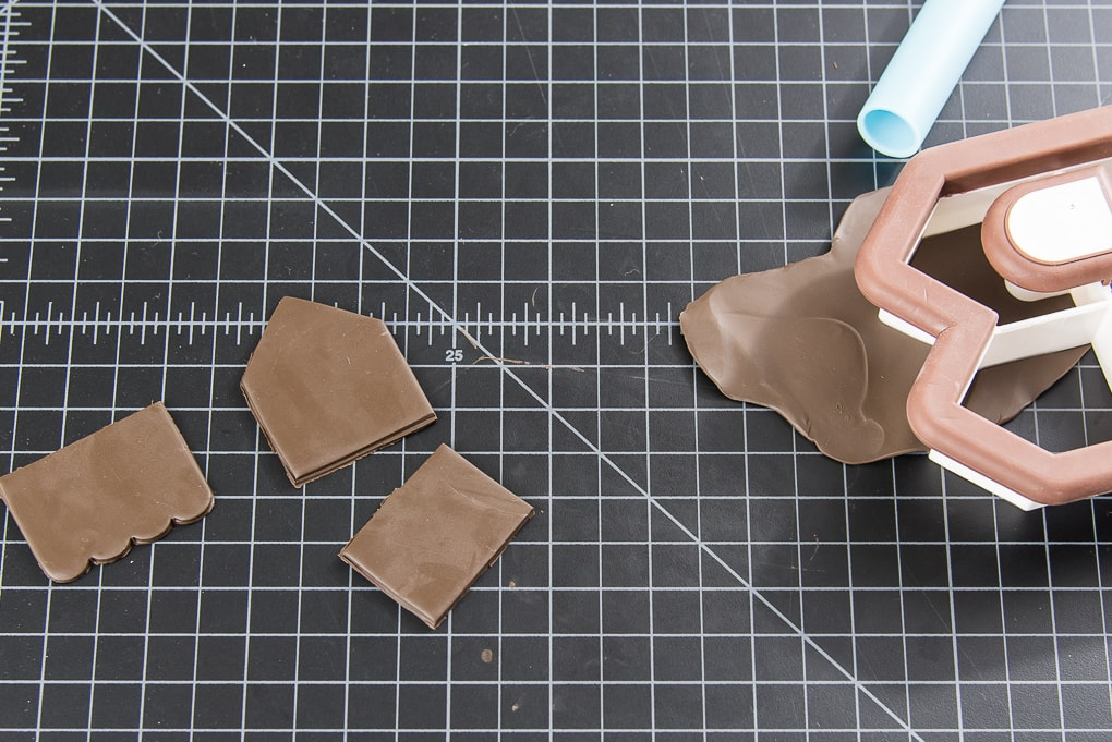 cutting gingerbread house walls out of brown clay