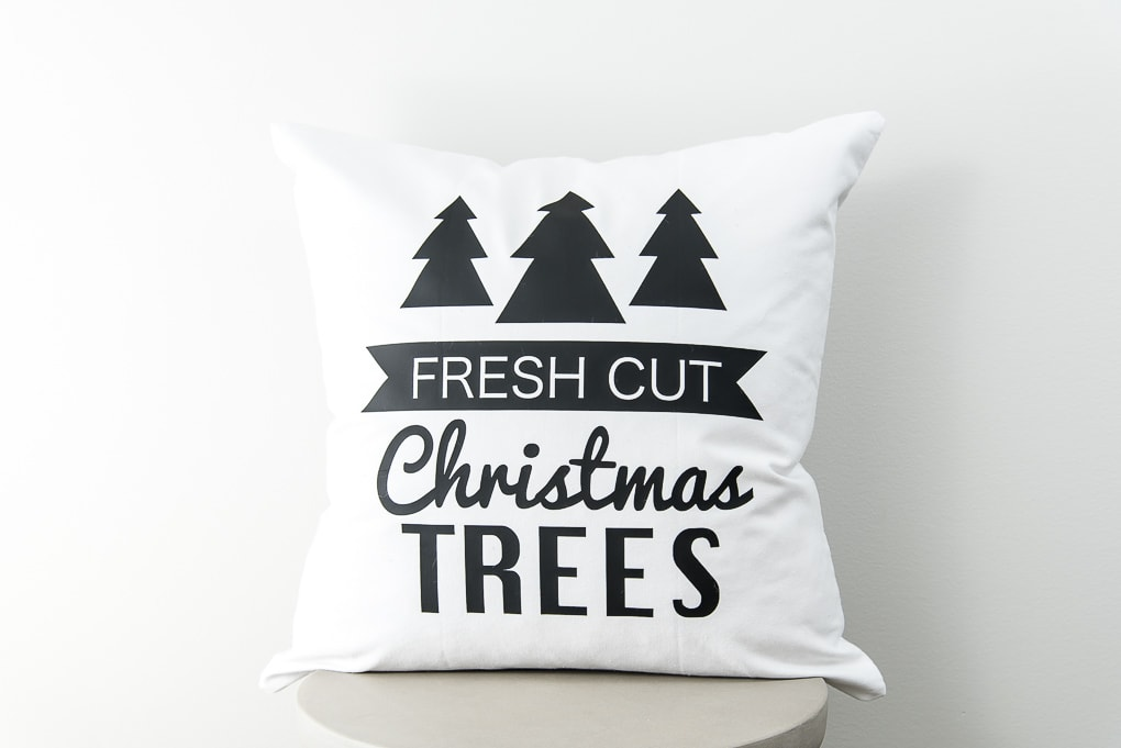 close up modern white pillow with black iron-on Christmas trees design