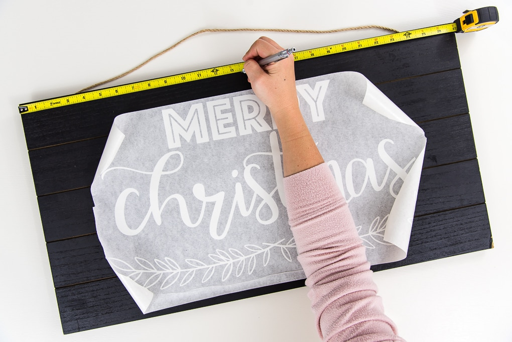 black wooden sign with white vinyl Merry Christmas design measuring tape