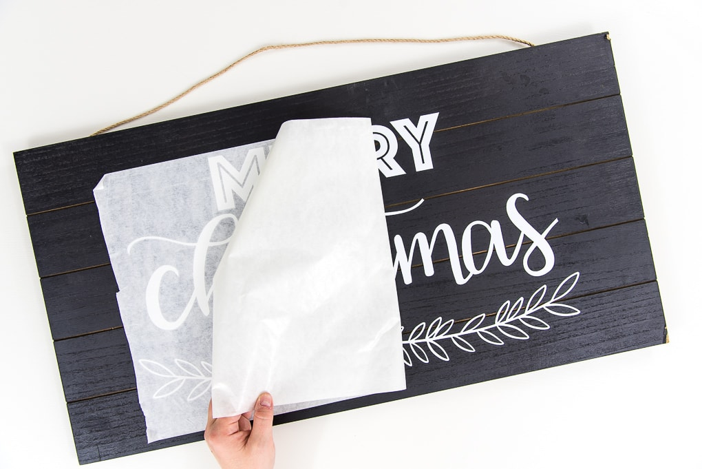 black wooden sign with white vinyl Merry Christmas design peeling off transfer tape