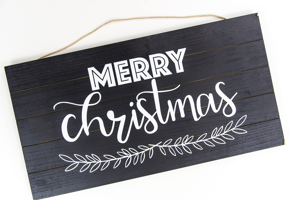 black wooden sign with white vinyl Merry Christmas design