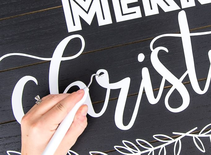 black wooden sign with white vinyl Merry Christmas design weeding detail with weeder tool