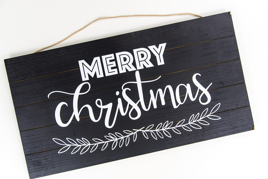 black wooden sign with white vinyl Merry Christmas design Cricut