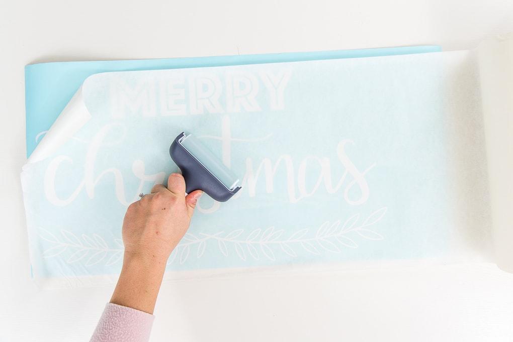 brayer tool on transfer tape over weeded white vinyl Merry Christmas design