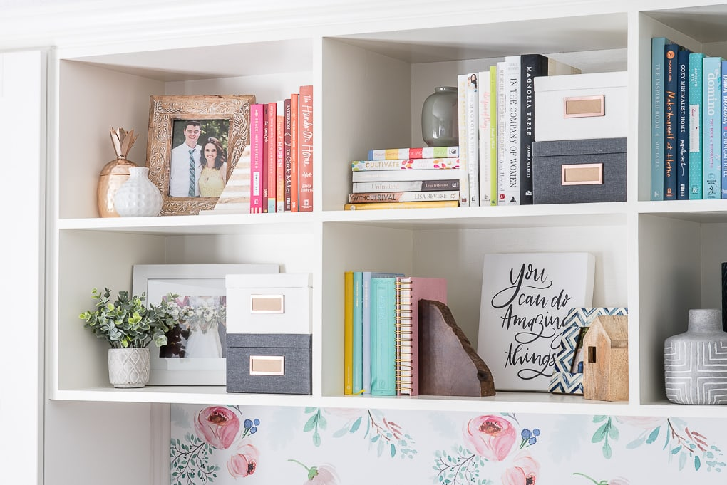 styled bookshelves with colorful books and picture frames