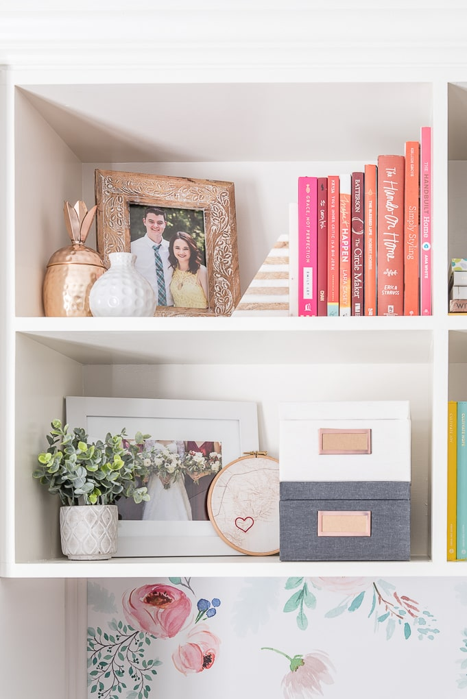 styled bookshelves with pink, red and gray accent pieces
