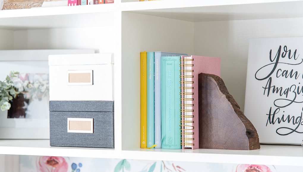 colorful books on a bookshelf with a wooden bookend