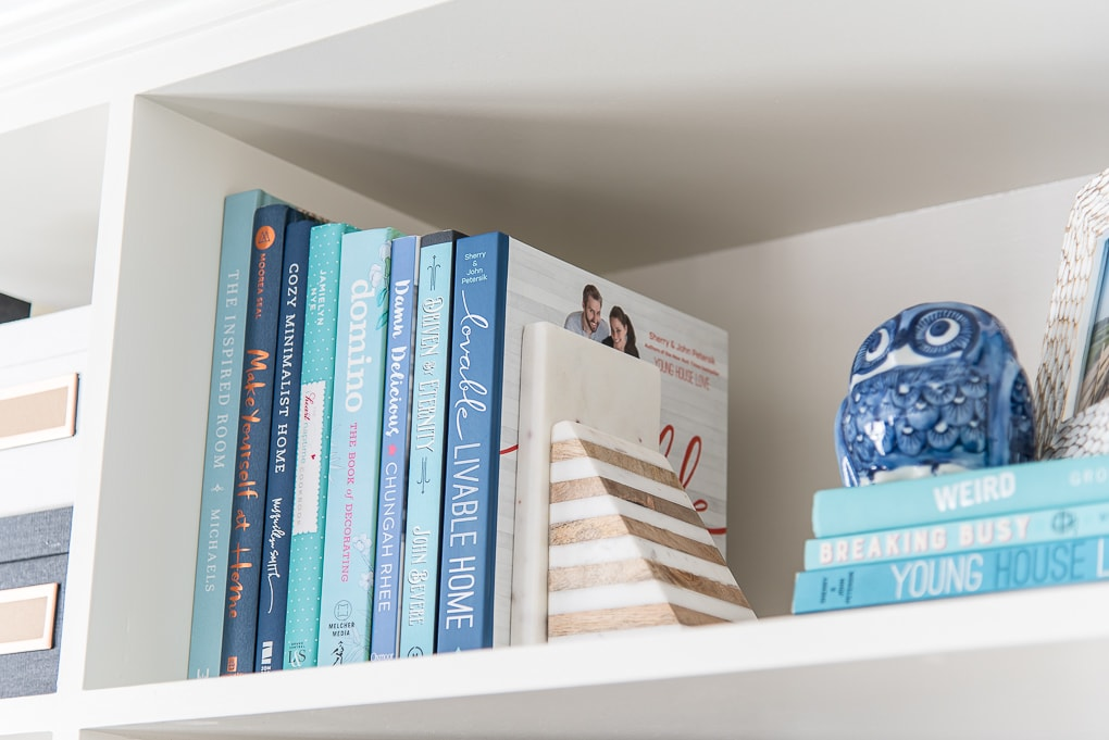 blue books on a shelf with a marble bookend
