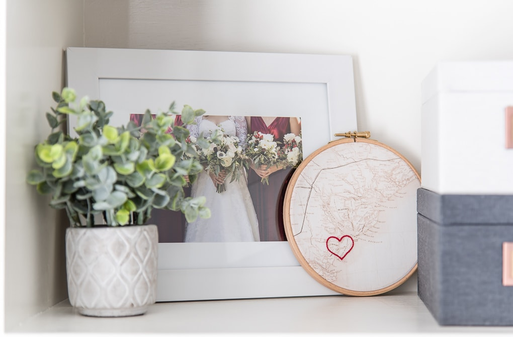 greenery on a shelf by a picture frame and embroidery loop