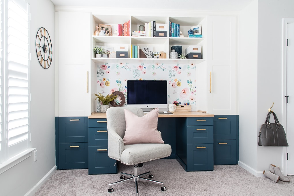 home office built-in desk navy and white with bookshelves and chair with pink pillow