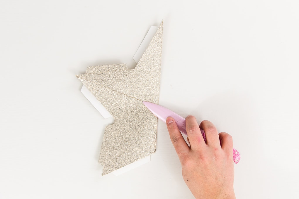 gold glitter star being folded with bone folder