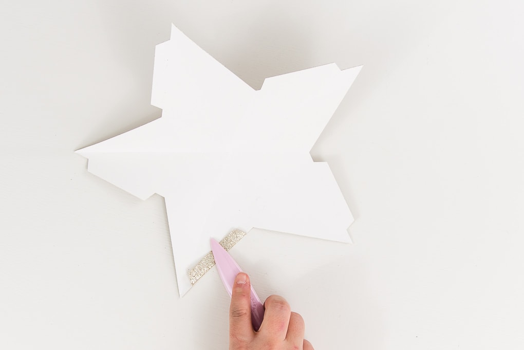 back of gold glitter star tabs being folded