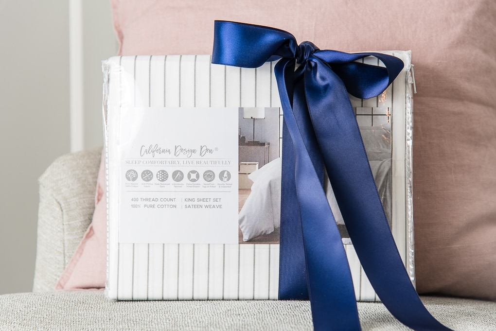 California Design Den white and gray striped sheets with a navy blue bow close up