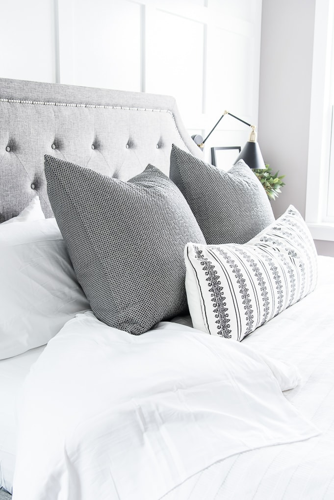 master bedroom bed white bedding gray pillows