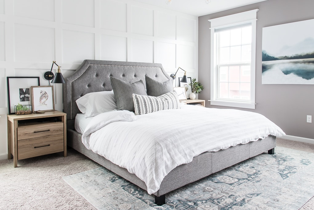 gray bed in a modern master bedroom white bedding