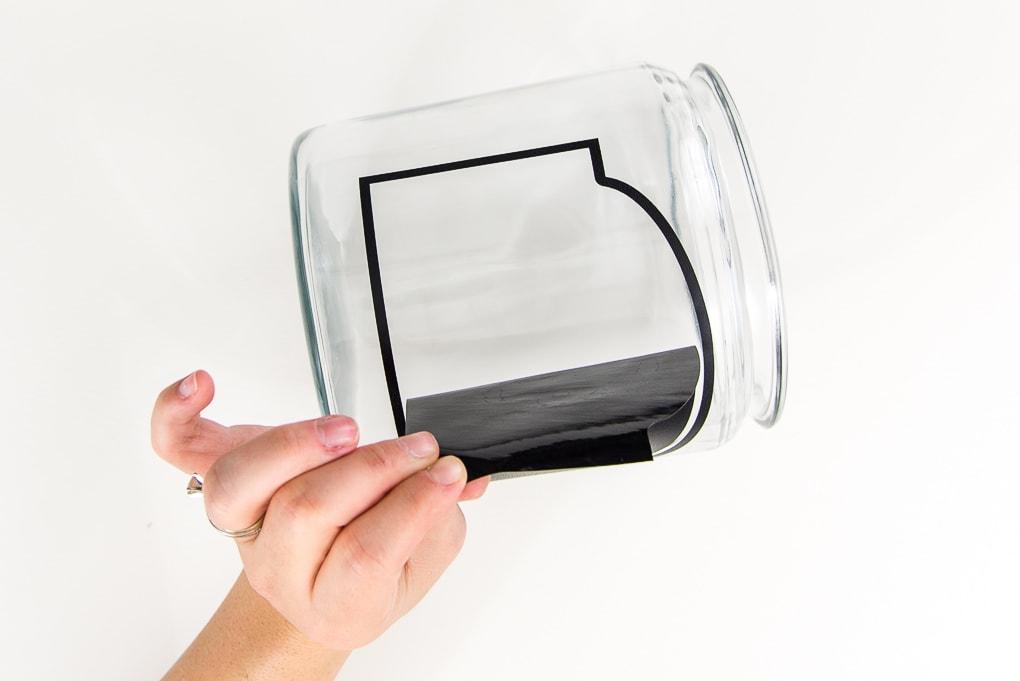 peeling chalkboard vinyl off glass jar with hand