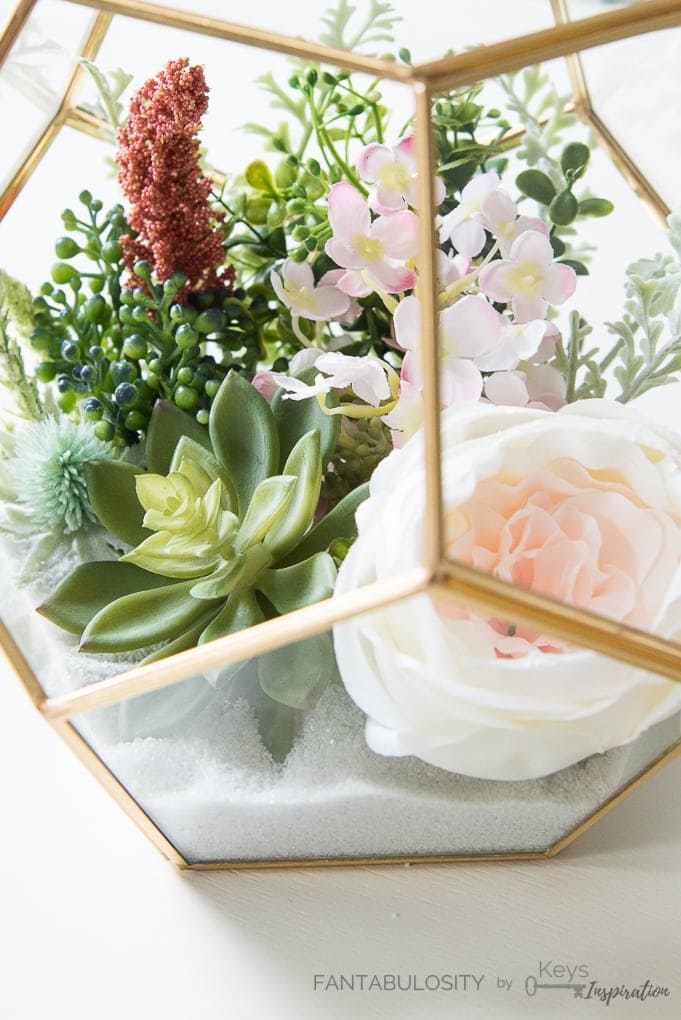 close up of gold terrarium with florals inside