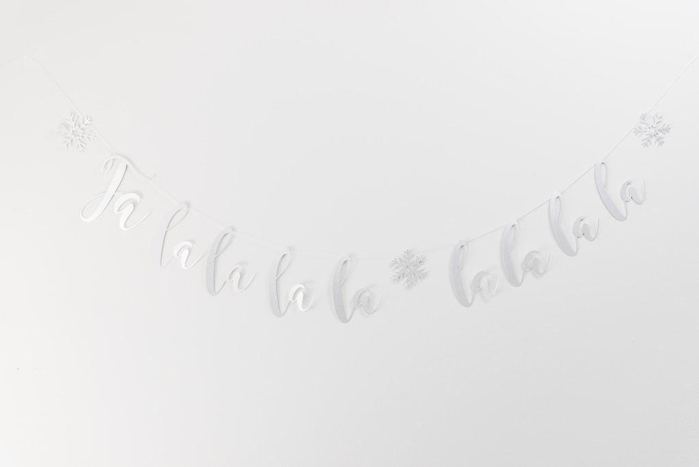 fa-la-la silver glitter banner on gray wall