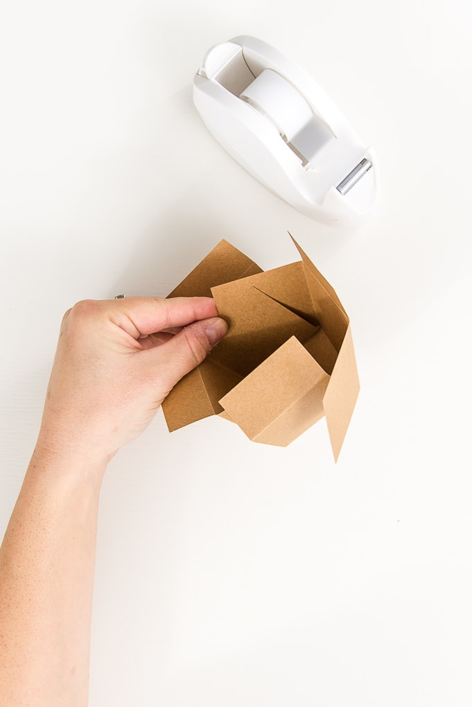 taping a brown 3D paper box