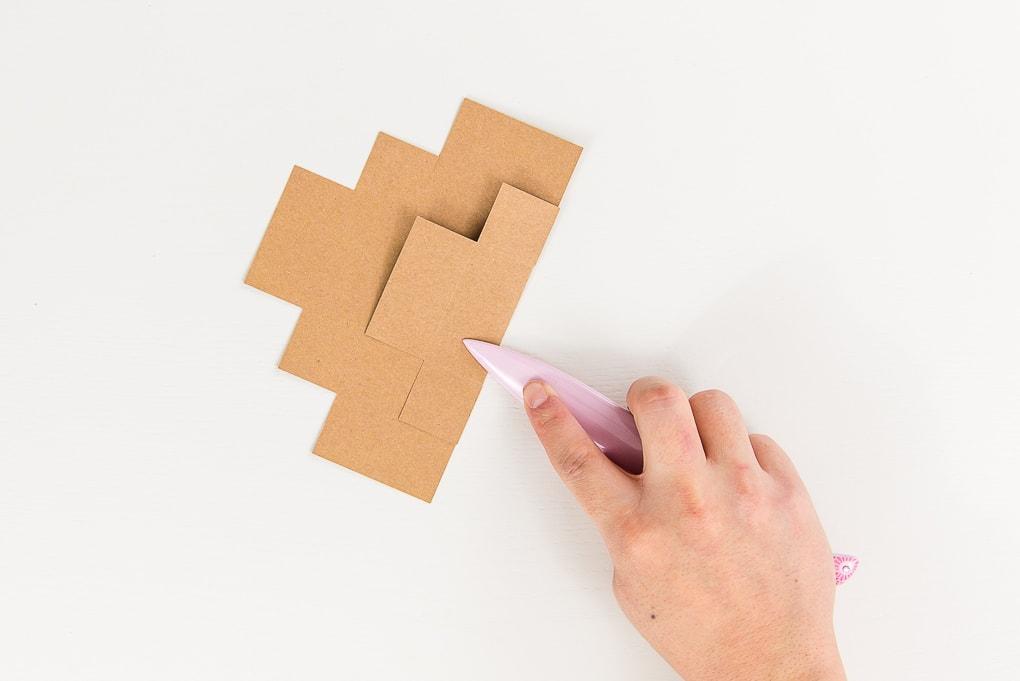 bone folder on brown paper box lid cutout
