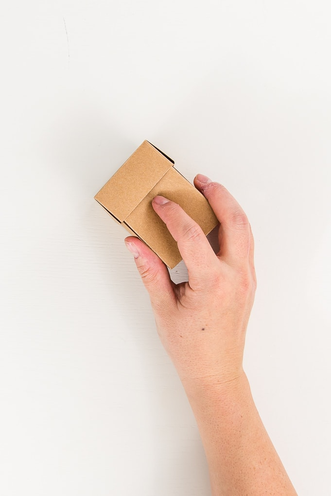 hand holding a brown 3D paper box and lid