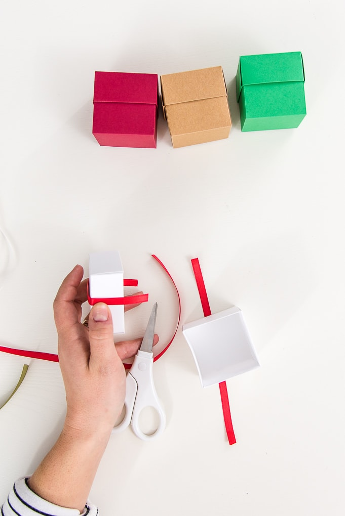 brown, white, red, and green 3D paper boxes cutting red ribbon