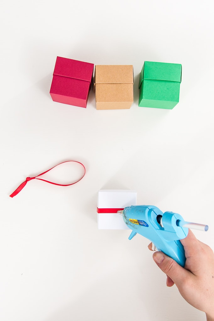 hot glue attaching red ribbon to white 3d box