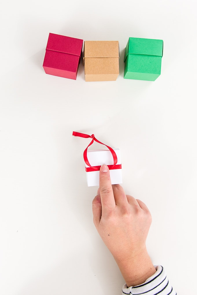 attaching red ribbon loop to the top of a white box