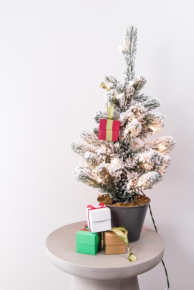 folding box gift ornaments next to flocked Christmas tree