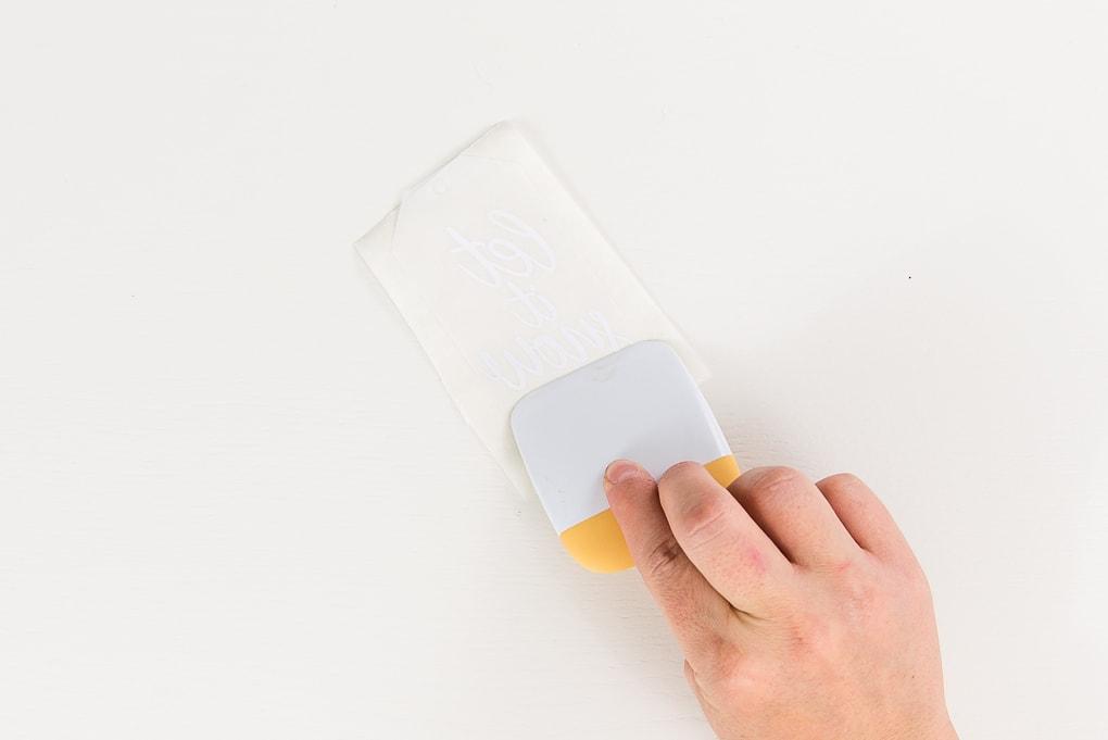scraper tool over white vellum tag