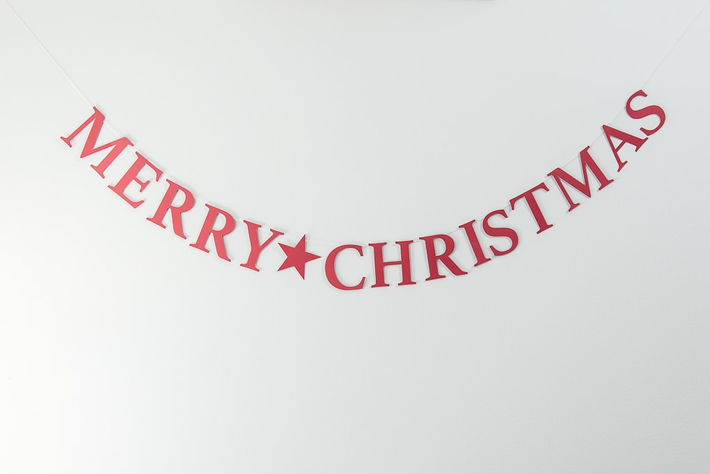 red Merry Christmas banner on gray wall