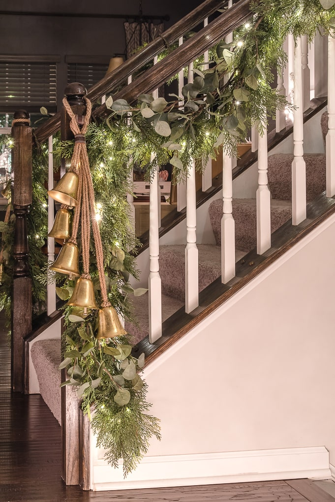 Christmas greenery garland on staircase with gold bells