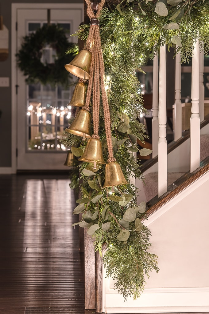 gold bells on greenery Christmas garland staircase
