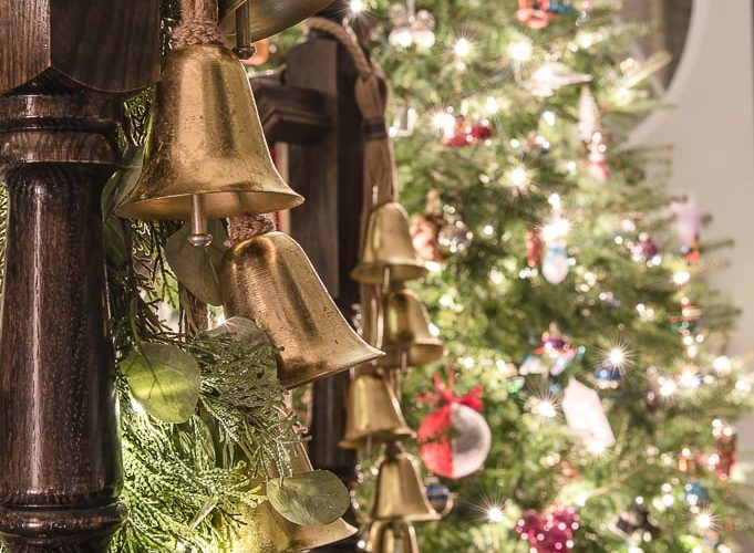 gold bells on Christmas garland with Christmas tree in the background