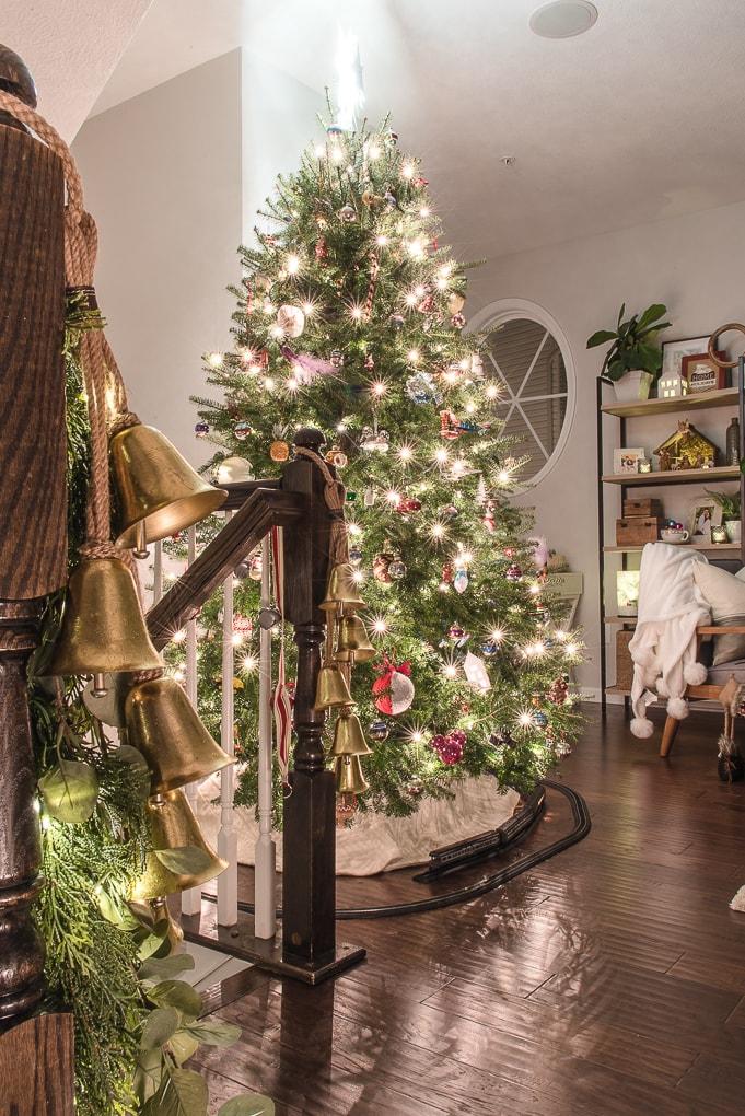gold bells on greenery garland at night lit up Christmas tree at night