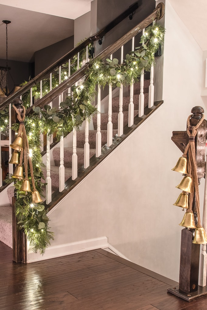 Christmas garland on staircase lit up at night with gold bells