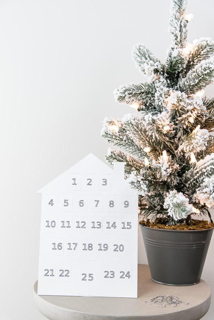 white house modern advent calendar next to flocked Christmas tree