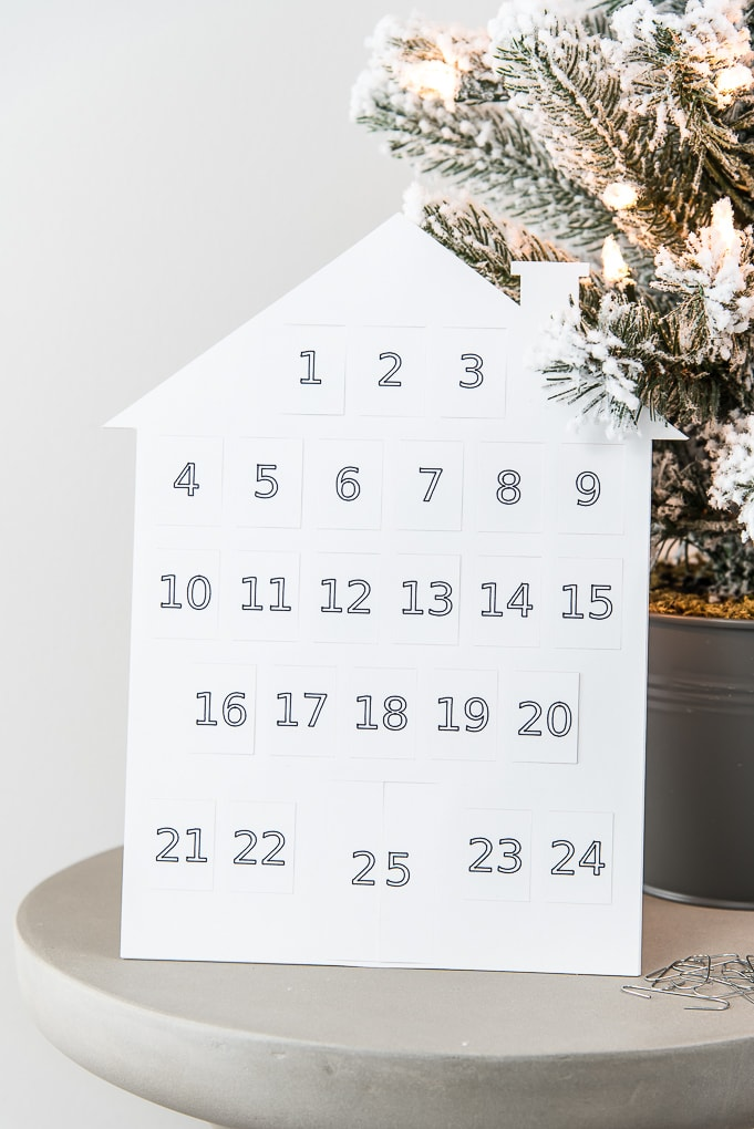 close up of white house modern advent calendar next to flocked Christmas tree