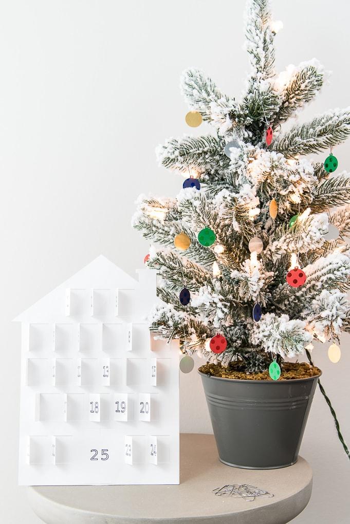white modern advent calendar doors open next to flocked Christmas tree
