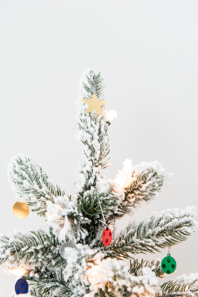 colorful mini star ornament on top of flocked Christmas tree