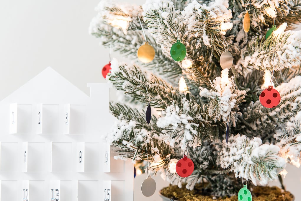 white advent calendar and colorful mini ornaments on flocked Christmas tree