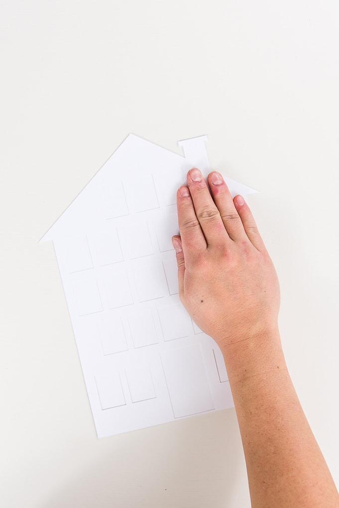 hand pressing glue on white house modern advent calendar