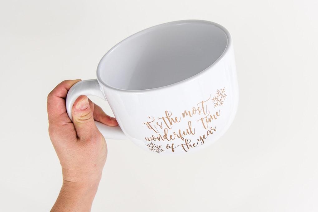 hand holding large white mug with gold adhesive vinyl design
