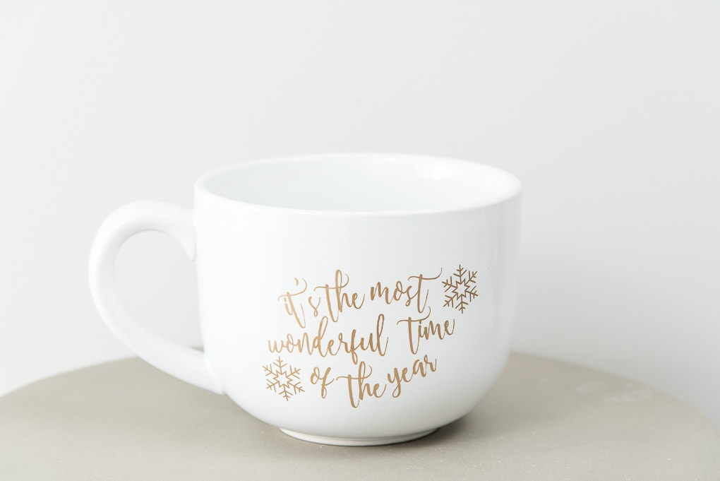 large white mug with it's the most wonderful time of the year gold adhesive vinyl design