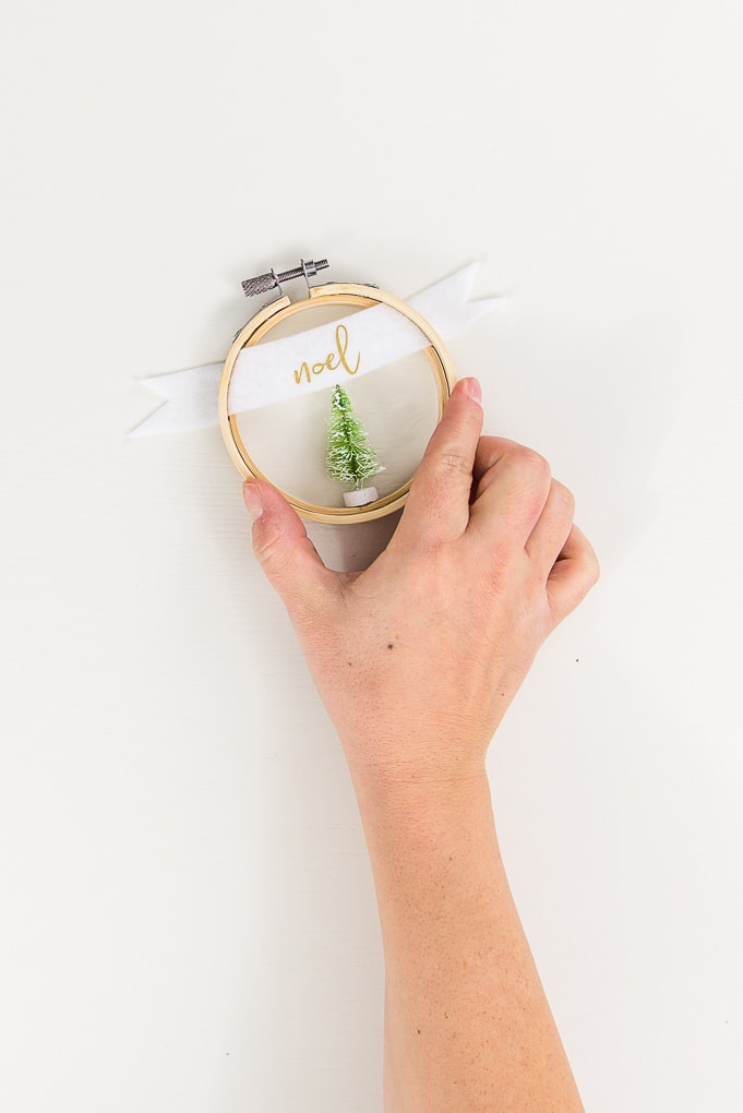 hand holding a noel embroidery hoop ornament