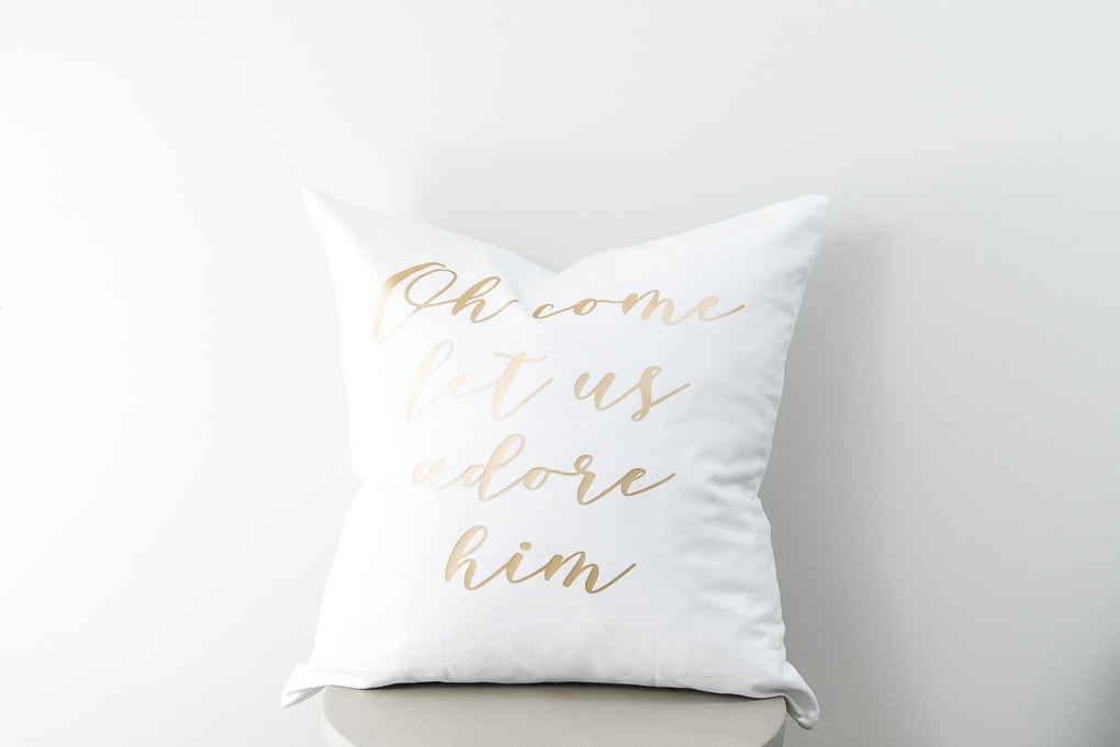 white Christmas let us adore him pillow with gold lettering