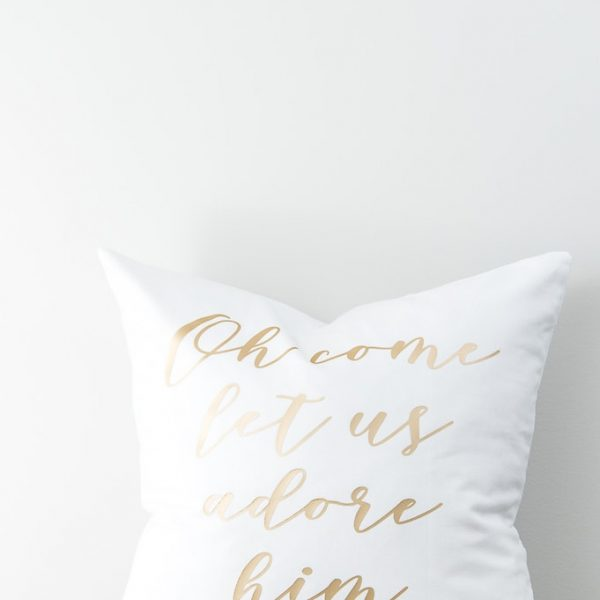 white Christmas pillow with gold lettering