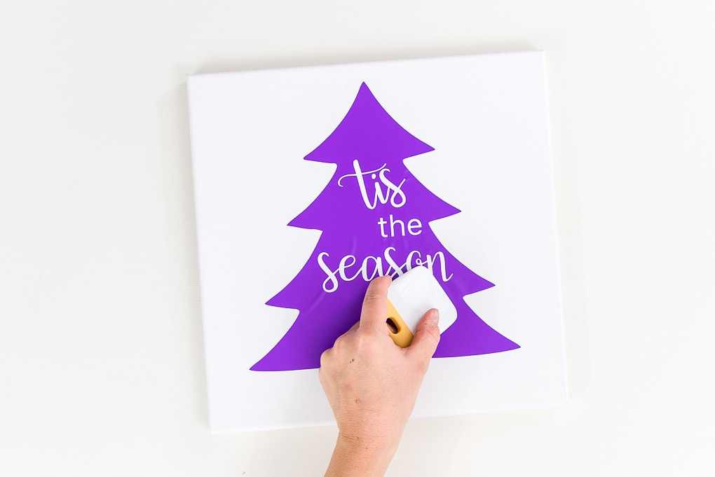 hand using scraper tool on purple vinyl canvas