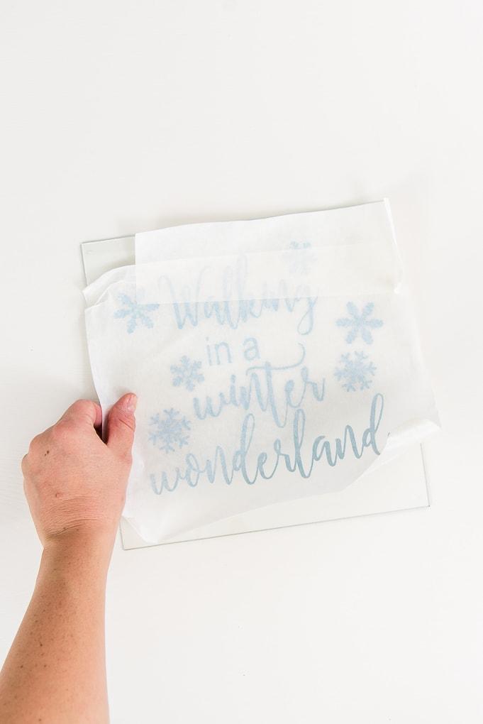 placing light blue vinyl design onto shadow box glass front